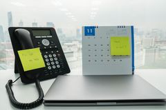 Stick note of call back message and check e-mail on IP phone and November calendar for employee reminder with computer stock photo