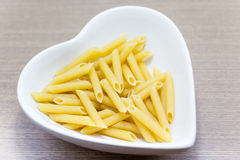 Stick pasta in a heart shaped bowl Stock Images