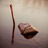 Stick and stone. A serenity-inspiring image of a pole and a rock  in a calm pool of water, illuminated by the warm sunset light Stock Photography