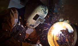 Stick welding. A craftsman stick welding pipe Royalty Free Stock Photo