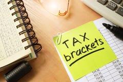 Stick with words tax brackets. Stock Photos