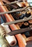 Sticka asken med många trådhjälpmedel och sax Arkivbild