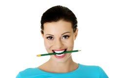 Stickande blyertspenna för fundersam attraktiv studentkvinna Royaltyfri Bild
