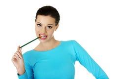 Stickande blyertspenna för fundersam attraktiv studentkvinna Arkivbild