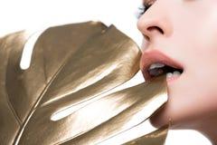 Stickande guld- blad för kvinna som isoleras på vit Royaltyfria Foton