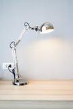 Stickaskrivbordlampa på det wood skrivbordet Royaltyfri Foto