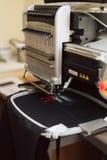 Stickender Text auf einer Nähmaschine auf einer industriellen Ebene Maschine stickt den Buchstaben f auf dem Gewebe stockbild