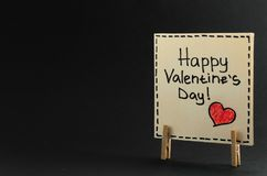 The sticker with the greeting happy Valentines day on the clothespin on a dark background Royalty Free Stock Photo
