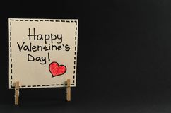 The sticker with the greeting happy Valentines day on the clothespin on a dark background Royalty Free Stock Photography