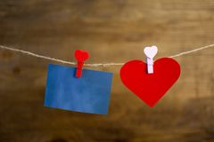 Sticker and little heart rests on the clothespin on the rope Stock Image