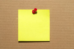 Sticker note. Yellow sticker note with a red push-pin over cardboard Stock Photography
