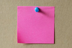 Sticker note. Pink sticker note with a blue push-pin over cardboard Stock Image