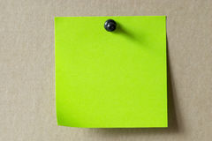 Sticker note. Green sticker note with a black push-pin over cardboard Royalty Free Stock Photo