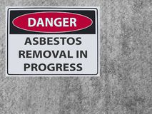 The sticker Sign danger asbestos removal on the plaster asbestos wall stock image