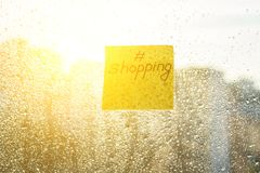 Sticker with text SCHOPPING. Background sunny window with shiny rain drops Stock Photos