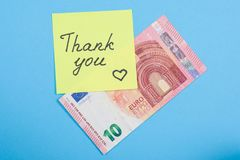 Sticker with word thank you, and cash money. Blue background Royalty Free Stock Photo