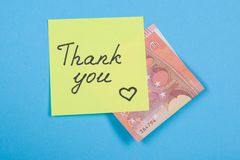 Sticker with word thank you, and cash money. Blue background.  Royalty Free Stock Photos