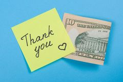 Sticker with word thank you, and cash money. Blue background Royalty Free Stock Images