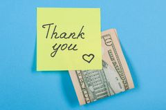 Sticker with word thank you, and cash money. Blue background Royalty Free Stock Photos