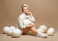 Stickerei. Frau, die in den weißen Baumwollstrickwaren mit Haufen-Bällen des Garns sitzt Lizenzfreies Stockfoto