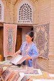 Stickerei- und Seidenteppich kaufen mit einer traditionsgemäß gekleideten Frau stockfoto