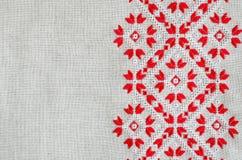 Stickereidesign durch rote und weiße Baumwolle verlegt auf Flachs Weihnachtshintergrund mit Stickerei lizenzfreies stockbild