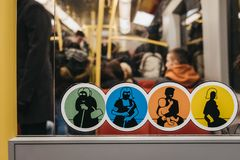 Stickers asking to give up seat to concessions inside tube carriage in Vienna, Austria. Vienna, Austria - November 25, 2018: Stickers asking to give up seat to stock photos