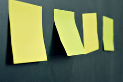 Stickers on the blackboard one in focus. Empty yellow highlight stickers for tittle or text Stock Photography