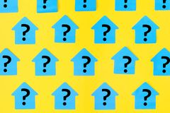 Stickers in the form of houses on a bright yellow background. On the blue sticky notes a question mark was written royalty free stock photos