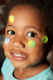Stickers on my face!. A young African-American child covered with stickers Royalty Free Stock Image