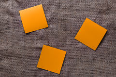Stickers on sackcloth. Orange stickers on dark sackcloth Stock Photo
