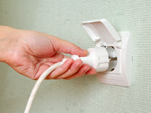 Sticking an electric plug in socket Royalty Free Stock Images