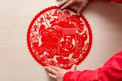 Sticking fluffy red flat paper-cut sticker as symbol of Chinese New Year of the pig the Chinese means good luck and bumper. Sticking a fluffy red flat paper-cut stock photo