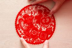 Sticking fluffy red flat paper-cut sticker as symbol of Chinese New Year of the pig the Chinese means good luck. Sticking a fluffy red flat paper-cut sticker as stock photo