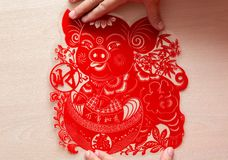 Sticking fluffy red flat paper-cut sticker as symbol of Chinese New Year of the pig the Chinese means everything is looking up. Sticking a fluffy red flat paper royalty free stock photography