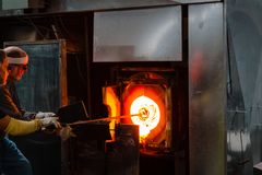 Sticking glass into the crucible furnace to heat it back up and shape it Royalty Free Stock Photography