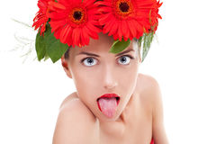 Sticking out tongue. Young beautiful woman wearing a gerbera wreath on her head sticking out her tongue stock images