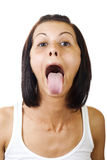 Sticking out tongue. A pretty young woman sticking out her tongue royalty free stock images