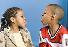 Sticking out tongues. Brother and sister playing Stock Photos