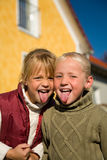 Sticking tongue out. Sisters sticking their tongue out at the viewer Stock Images