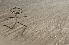 Stickman, das auf dem Sand läuft Stockfotografie