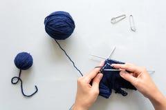 Stickor för hatt för flickaräta maskor blåa på grå träbakgrund Process av handarbete royaltyfria bilder
