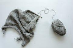 Stickor för tröja för flickaräta maskor gråa på grå träbakgrund Process av handarbete royaltyfria bilder