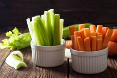 The sticks of carrots and celery in white bowls royalty free stock photo