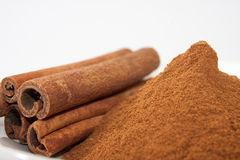 Sticks of cinnamon and cinnamon powder in a bowl Royalty Free Stock Photo