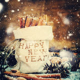 Sticks of Cinnamon in a Linen Bag Embroidered with Happy New Year. Drawn snow Royalty Free Stock Images