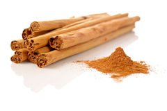 Sticks and powder of cinnamon. Reflected on the white background. Shallow DOF Stock Photo
