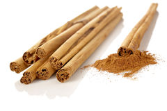 Sticks and powder of cinnamon. Reflected on the white background. Shallow DOF Stock Photos