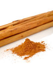 Sticks and powder of cinnamon. Reflected on the white background. Shallow DOF Stock Image