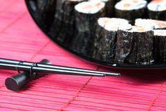 Sticks for sushi. On a red bamboo napkin beside plate of sushi Royalty Free Stock Photo